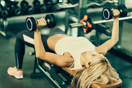 toned image: Beautiful young woman lying on the bench, working out with weights in modern gym. Toned image