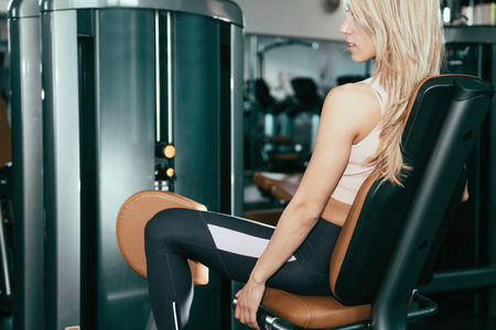 abductor: Adduction or abductor machine - Attractive girl exercising her thighs in the gym