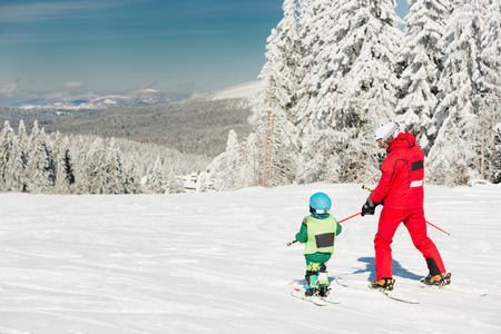 downhill: Little boy skiing downhill with ski instructor