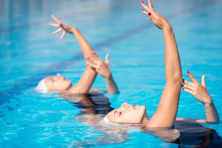 performing: Synchronized swimming duet performing in swimming pool Stock Photo