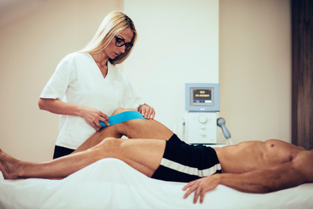 tarsus: Kinesio taping in physical therapy - therapist placing kinesio tape to patients knee Stock Photo
