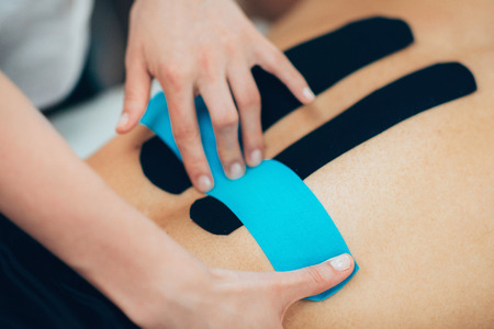 Physical therapist placing kinesio tape on patient's back