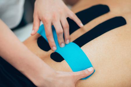 환자의 뒷면에 kinesio 테이프를 배치 물리 치료사 스톡 콘텐츠