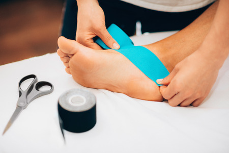 tarsus: Kinesio taping in physical therapy - therapist placing kinesio tape to patients foot Stock Photo