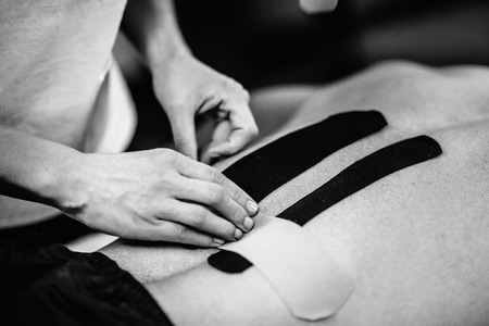 Physical therapist applying kinesio taping onto patients lower back