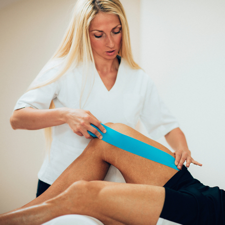 taping: Kinesio taping in physical therapy - therapist placing kinesio tape to patients knee Stock Photo