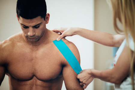 Physical therapist placing kinesio tape, placing it onto patients shoulder