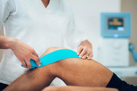 환자의 무릎에 kinesio 테이프를 배치 물리 치료사 스톡 콘텐츠
