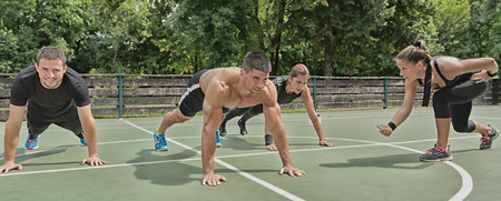 push ups: Female exercising instructor motivating students to do more push ups Stock Photo
