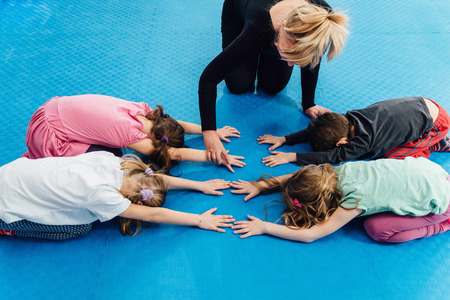 posture correction: Physical education - Teacher working with group of little school children, exercising spinal flexibility, improving body posture, positively influencing growth and development
