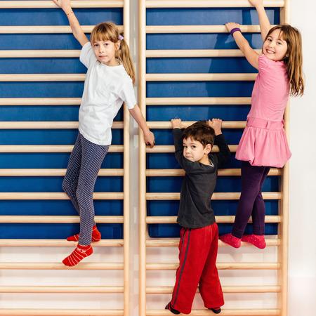 Petits enfants escalade espalier dans le gymnase de l'école Banque d'images - 56462636