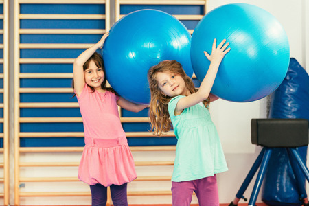 physical education: Two girls at physical education class, playing with fitness balls