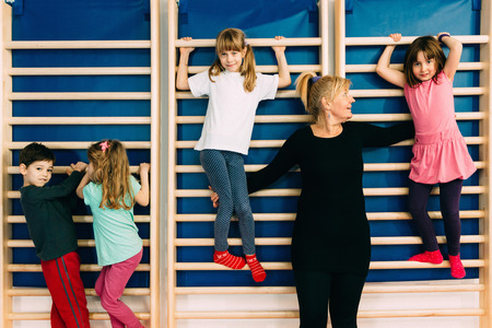 corrective: Children and physical therapist at corrective gymnastics class. Climbing wall ladders