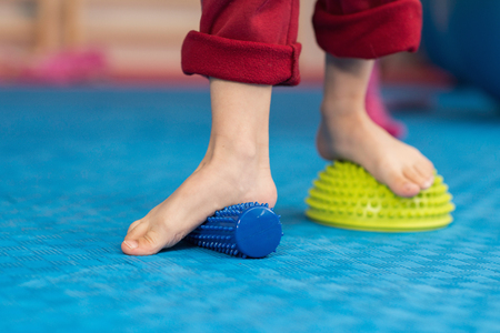 Piedi piatti terapia fisica - Ragazzino salire su rullo di gomma a spillo