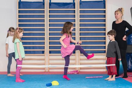 educacion fisica: Pequeños niños que juegan con la banda elástica en la clase de educación física