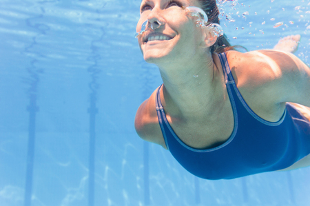 Young woman swimming underwater, looking up