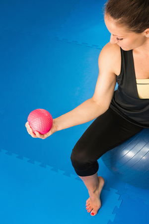 only the biceps: Woman working out with exercise ball Stock Photo