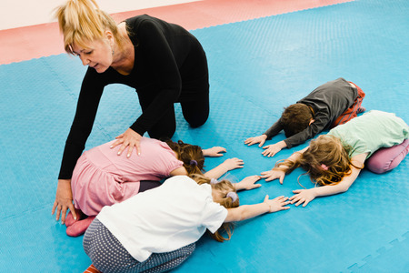 corrective: Group of children doing corrective exercises with therapist