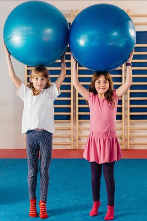educacion fisica: Dos niñas en la clase de educación física, jugando con bolas de la aptitud
