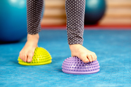 spikey: Flat feet correction exercise - Little girl walking over spikey half balance rubber balls on a physical therapy exercise class
