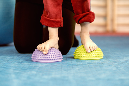 spikey: Flat Feet Corrective Exercises - Little boy walking over spikey half balance rubber balls on a physical therapy exercise class