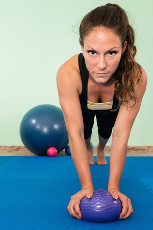 fitness ball: Young woman exrecising, practicing balance with fitness ball
