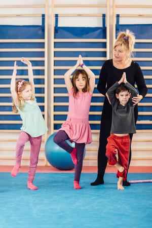 educacion fisica: Grupo de niños pequeños con el maestro en la clase de educación física. Intenta ponerse de pie sobre una sola pierna, manteniendo el equilibrio