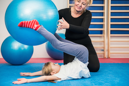 posture correction: Physical therapist working with little girl in school gymnasium, exercising with fitness ball