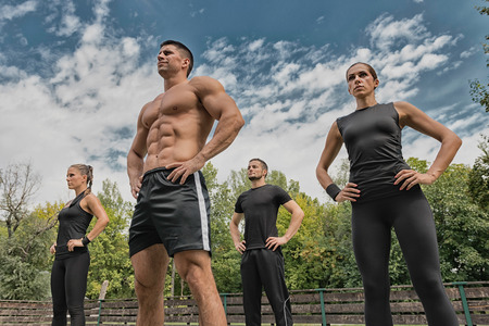 cardiovascular workout: Fitness instructor posing with his team