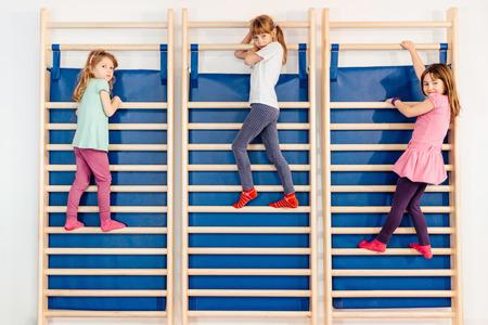 wall bars: Three little girls climbing on wall bars in school gymnasium