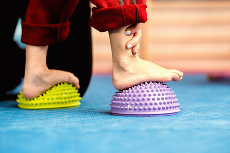 Flat Feet Corrective Exercises - Little boy walking over spikey half balance rubber balls on a physical therapy exercise class. Physical therapist helping