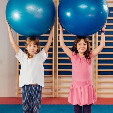 educacion fisica: Las niñas en la clase de educación física, jugando con pelotas para ejercicios, tratando de pie alto. imagen de tonos