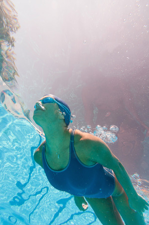 Underwater image of attractive female swimmer above the camera. Strange purple sunlight effect. Looking closely reveals body silhouette on the inner water surface.