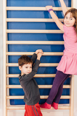 wall bars: Little children hanging on wall bars in school gymnasium Stock Photo