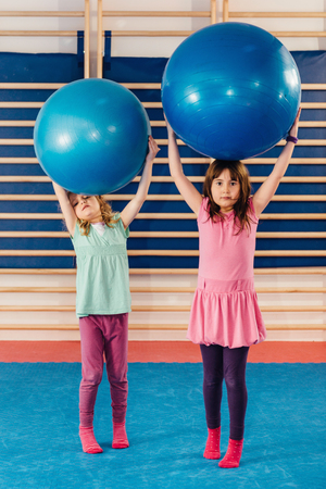 physical education: Little girls at physical education class, playing with fitness balls, trying stand tall. Toned image