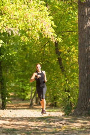 vertical wellness: Female athlete jogging in park Stock Photo