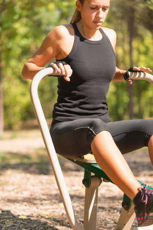vertical wellness: Workout on outdoor rowing machine, selective focus Stock Photo