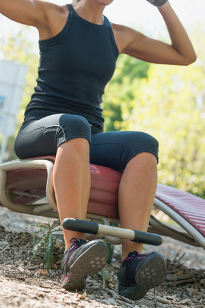 situp: Female athlete doing sit ups on sit-up board in metropark