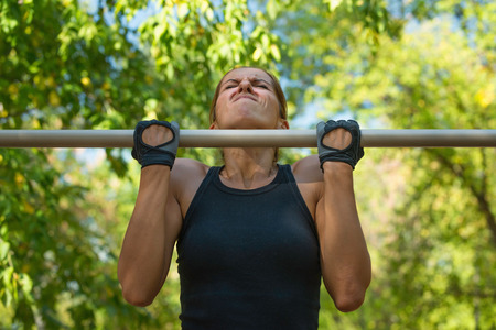 pull up: Pull ups by female on pull up bar in metropark
