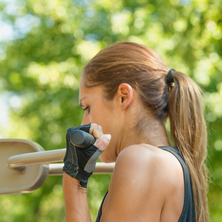 pullups: Female athlete doing pull-ups outdoors, focus on hand