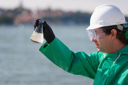 Sample of polluted water in environmentalists hand Stock Photo