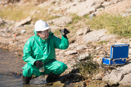environmentalist: Environmentalist with samples of polluted water on the shore Stock Photo