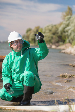 environmentalist: Environmentalist looking at sample of polluted water collected by the drainage hose Stock Photo