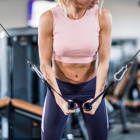 crossover: Attractive female athlete exercising on cable crossover in the gym Stock Photo
