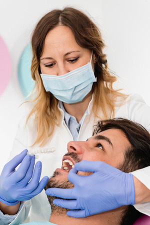 orthodontist: Orthodontist working with patient, placing invisible braces