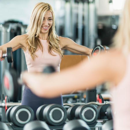 mirror image: Attractive woman exercising with weights in the gym. Looking in the mirror, satisfied with her progress. Toned image Stock Photo