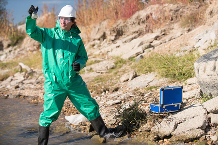 Environmentalist in protective suit holding sample of polluted waterwater Stock Photo