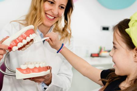 Dentist with little girl, explaining importance of dental hygiene