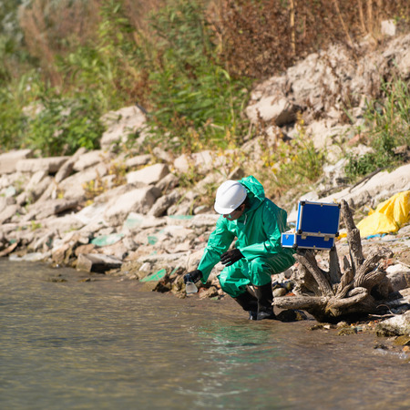 protective suit: Environmentalist in protective suit taking sample of water