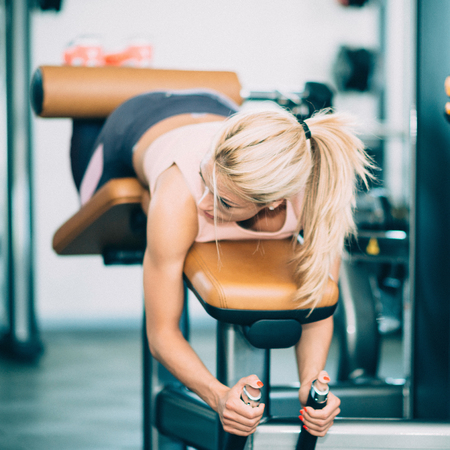 hamstrings: Attractive female athlete exercising on lying leg curls machine in the gym